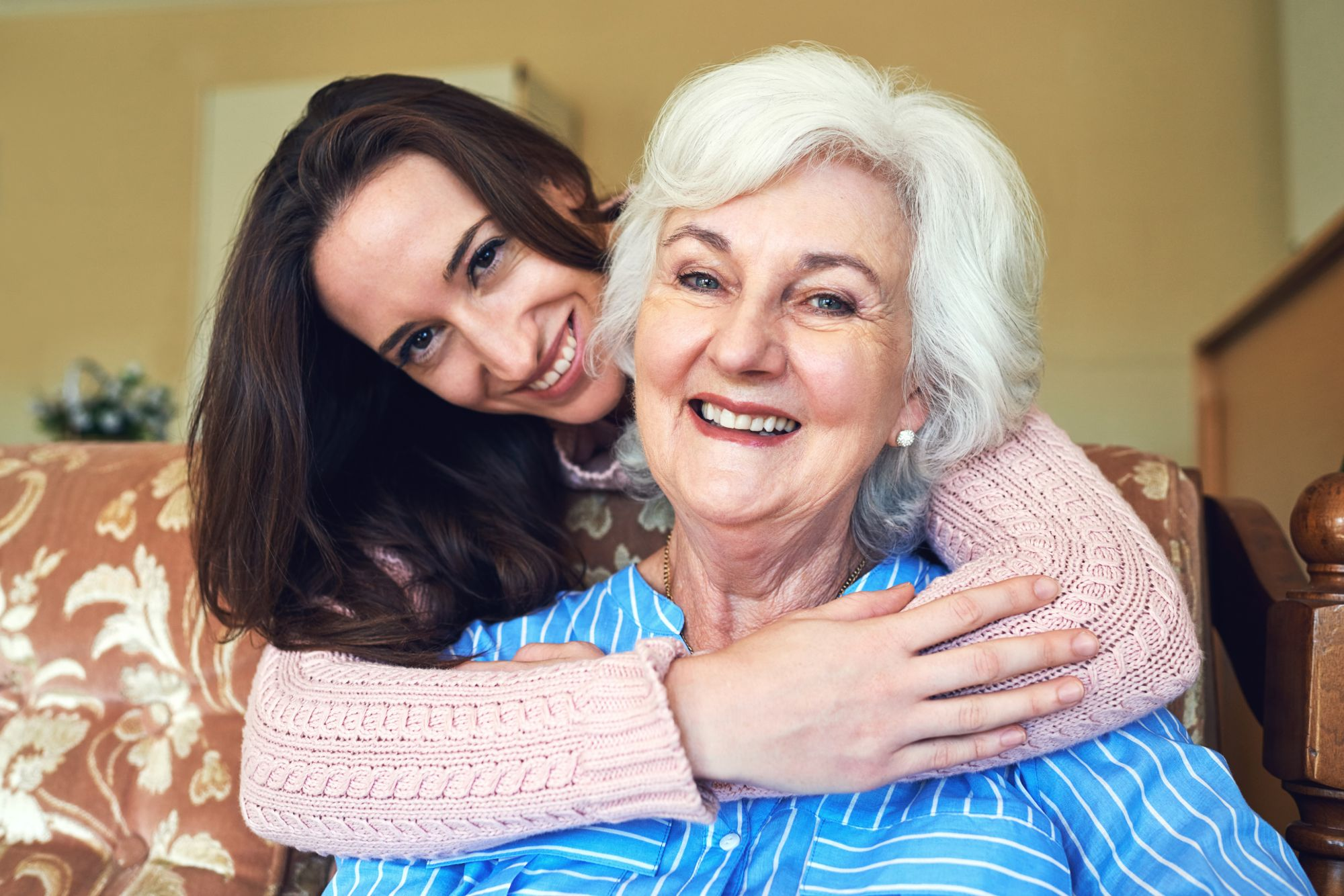 Assisted Living resident with granddaughter who is hugging her from behind